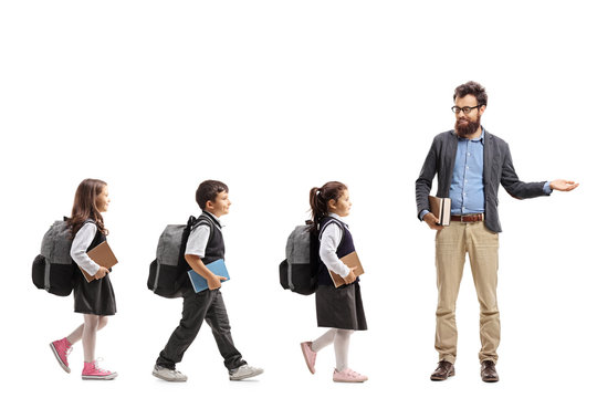 Schoolchildren walking in a line and a teacher gesturing welcome with his hand