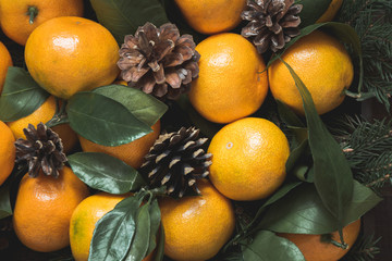 Fresh mandarins with leaves and pine cones. Healthy eating concept for winter. Close up.