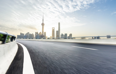 empty asphalt road with city skyline