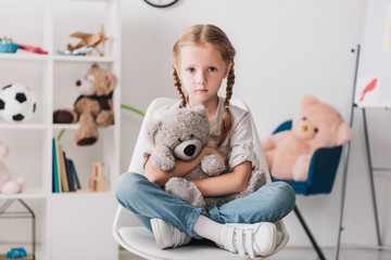 lonely little child sitting on chair and embracing her teddy bear while looking at camera