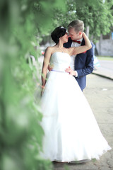 bride and groom hugging each other,standing on a city street