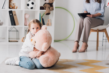 scared little child with teddy bear sitting on floor with psychologist sitting on background