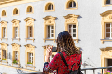 Rear view of young tourist woman visiting picturesque destination city on holiday, pointing smart phone camera, taking pictures, networking outdoors.