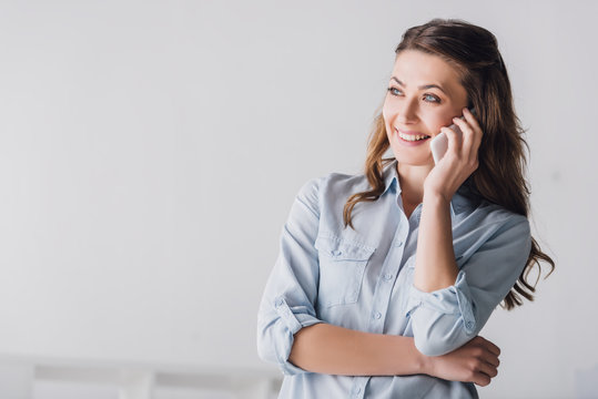 close-up portrait of smiling adult woman talking by phone and looking away