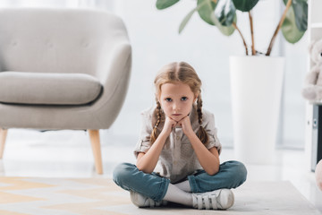 lonely depressed little child sitting on floor of empty room and looking at camera