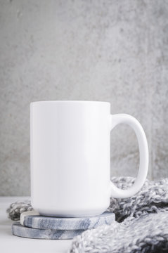15 oz mug mockup with marble coasters and a grey blanket