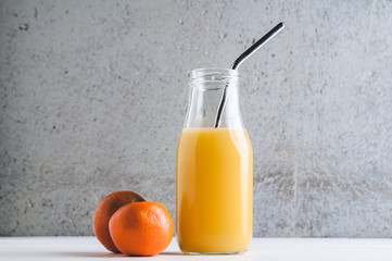 orange juice in a bottle with a reuseable metal straw