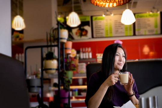 Mid adult woman holding coffee cup in cafe