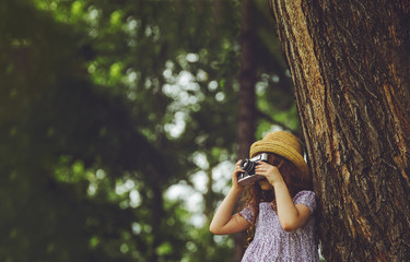 Little girl in straw hat, rustic style dress with retro photo camera in summer park.