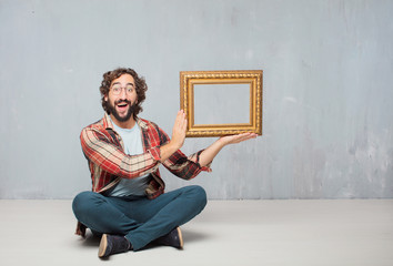 young crazy mad man  fool pose holding a baroque frame