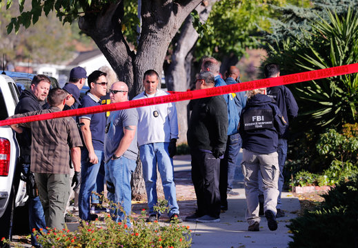 Police and FBI officer await a search warrant outside the home of the suspect in a shooting incident at a Thousand Oaks bar, in Newbury Park