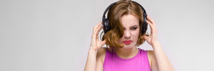Charming young girl in pink dress on gray background. Young girl with headphones unhappy
