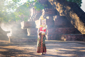 Beautiful Thai Young woman in traditional dress costume with thai style temple background.