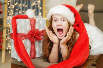 Surprised little girl in Santa hat. Christmas concept.