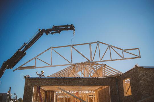 Builder directing crane positioning frame over building