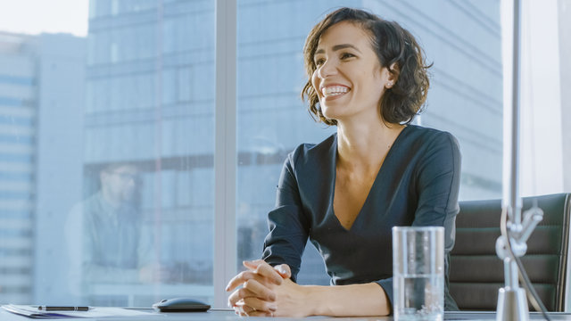 Portrait of a Beatiful Young Businesswoman Smiling Charmingly to Her Potential Business Partner. Strong Independent Woman in Business Situation.