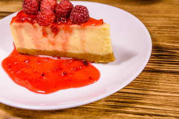 White plate with cheesecake New York and raspberries on wooden table