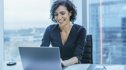 Portrait of the Successful Smiling Businesswoman Working on a Laptop in Her Office with Cityscape View Window. Beautiful Independend Female CEO Runs Company. Wall mural