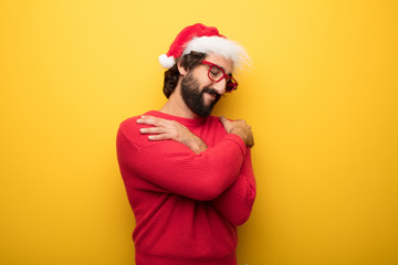 young crazy bearded man wearing red glasses and santa claus hat