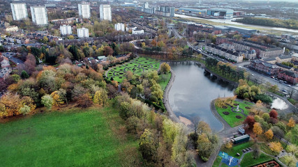 Aerial image over the pond in Victoria Park in Glasgow on bright autumn day.