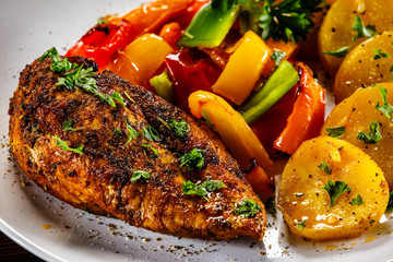 Grilled chicken fillet and vegetables on woowde table