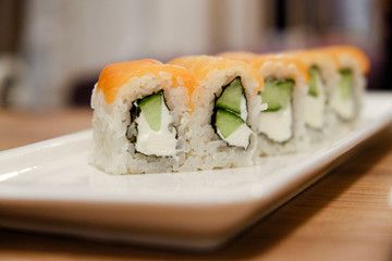 Horizontal shot of a close-up of rice rolls with salmon, cucumber and cream cheese on a white porcelain stretched rectangular dish on a wooden table in natural light colors.