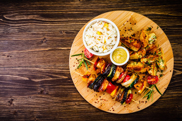 Kebab - grilled meat and vegetables on cutting board on wooden table