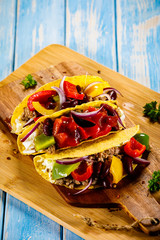 Tacos on cutting board on wooden table