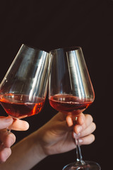 hand holds a glass of fresh red wine on a dark background