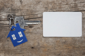 Key with house icon and white blank paper on wooden background
