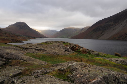 Sunlight falls on Great Gable mountain side out of an overcast and cloudy sky set against the dark lake of Wastwater (Wast Water) and scree valley sides, Lake District, Cumbria, UK