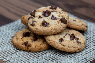 delicious cookie with chocolate drops, over wooden table and rustic tin.