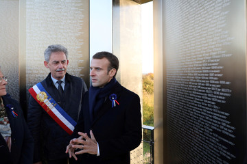 "French President Emmanuel Macron speaks flanked by  Mayor of Ablain-Saint-Nazaire Dominique Robillart Dominique as they visit ""Ring of Memory"" international World War I memorial, at the Notre Dame de Lorette French War Cemetery near Arras"