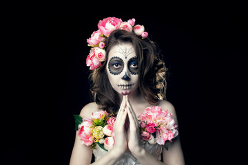 Young girl with a make-up on halloween with a wreath of peonies. Holding hands in front of a gesture of prayer.