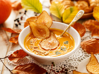 Pumpkin soup with the addition of pear chips in a white ceramic bowl. Delicious and healthy vegetarian soup
