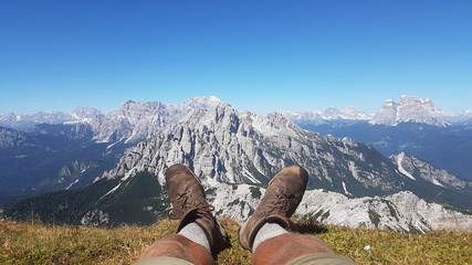 Hiking boots having fun and enjoying wonderful breathtaking mountain view. Freedom concept in alps mountain with snow on peak.