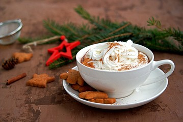 Hot cocoa in a white cup in a New Year's decoration on a brown background. Served with ginger biscuits and whipped cream.