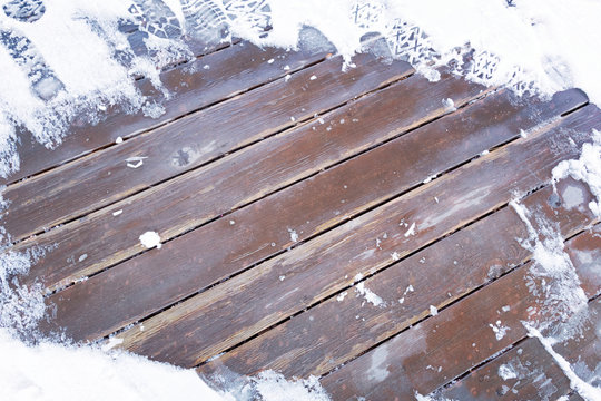 Foot prints on brown wooden deck partially covered with snow