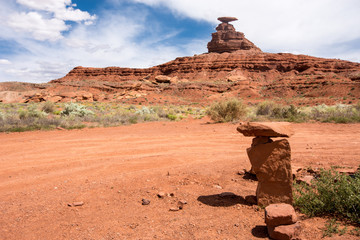 Rock cairns and the Mexican Hat rock formation in the Utah desert of the Four Corners region