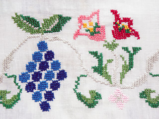 Ukrainian embroidery, embroidered flowers and a bunch of grapes of white fabric