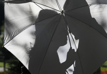 Lovers couple shadow silhouette reflected on the white umbrella against the l