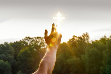 A hand is reaching a glowing cross image which is situated in the sky above the green summer trees.