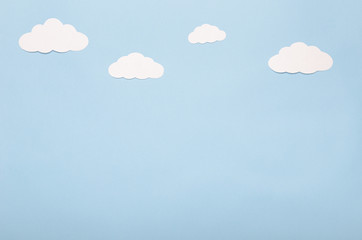 White paper clouds on a blue background. Application, the sky.