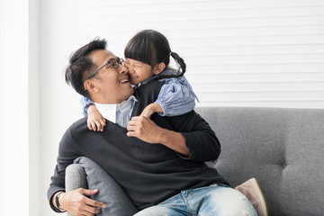 Asian father and daughter playing and kiss together in livingroom at home.