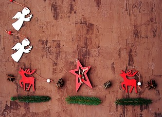 Christmas and New Year composition. Christmas toys in the form of stars, angels and deer, green branches of tree, cones on a brown background. Winter holiday concept. Flat lay, top view. Copy space.
