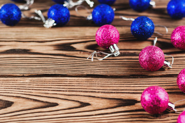 Lot of scattered red and blue christmas balls on old wooden table. Top view
