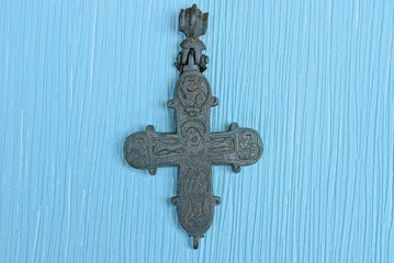 one old bronze cross encolpion lies on a blue table