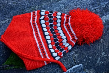 colored wool hat with a pompon lies on gray asphalt