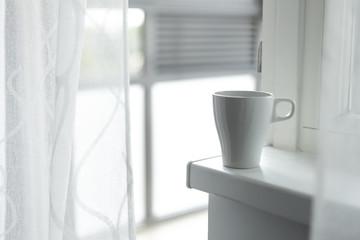 A cup of coffee on the windowsill. Big window. Scandinavian style