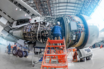 Airplane mechanic diagnose repairs jet engine through open hatch.